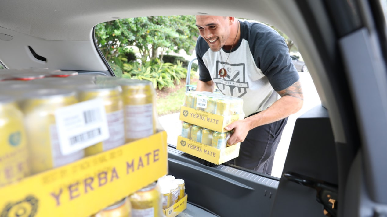 A man loads a case of Yerba Mate beverages into the back of a Chevrolet Bolt EV Cargo.