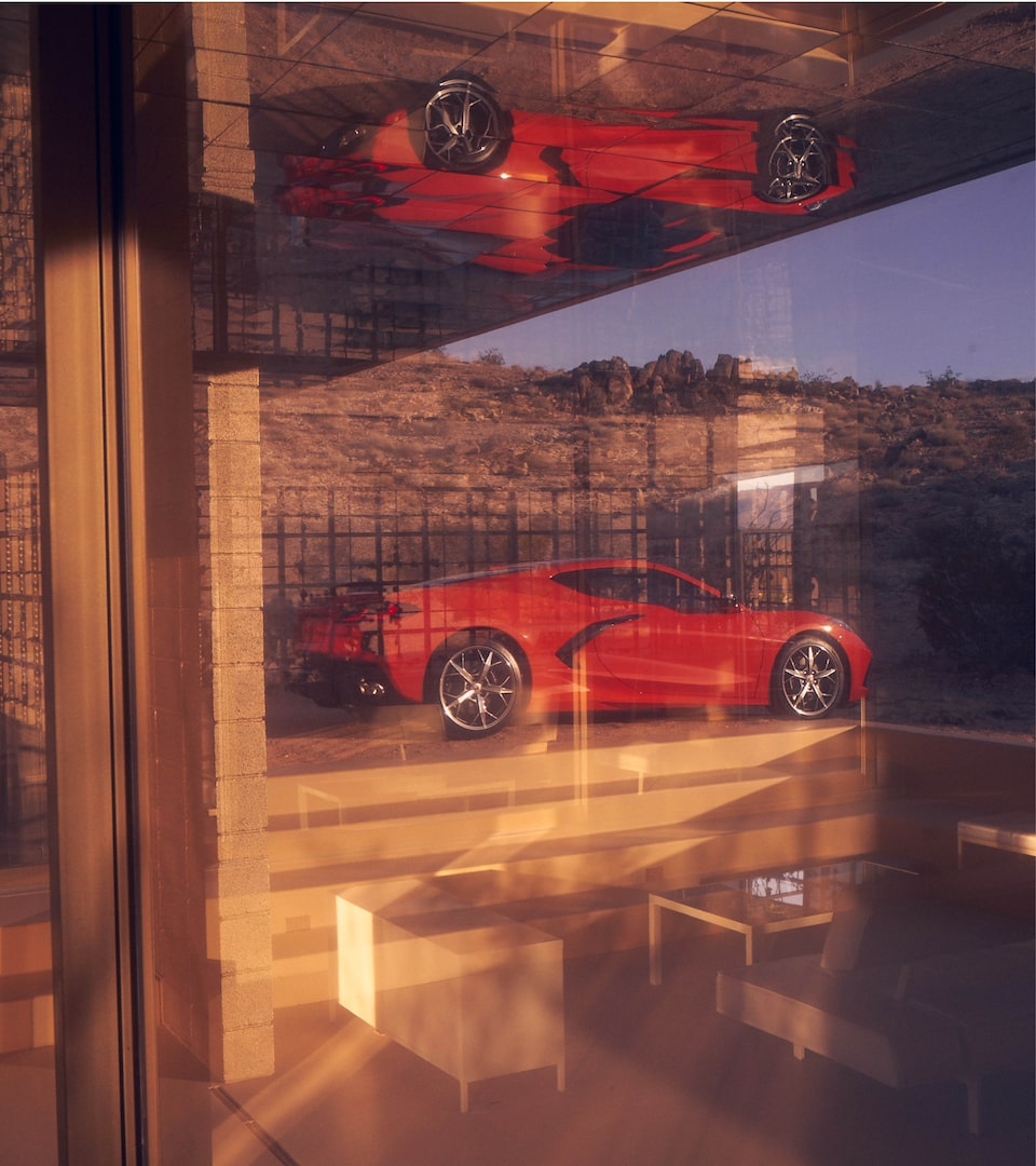 A Torch Red 2020 Corvette coupe sits in a desert landscape, seen through a window. A reflection of the car is in the glass.