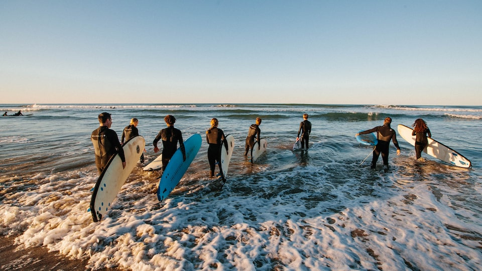 A group of people wearing wetsuits and carrying surfboards walk into the ocean.