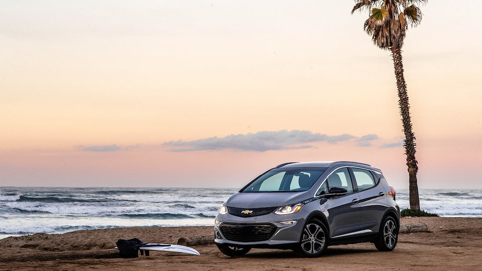 A Bolt EV sits on the beach with a single palm tree and the ocean in the background.