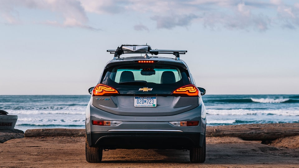 A Bolt EV seen from behind in a beach parking lot looking out at the ocean beyond.