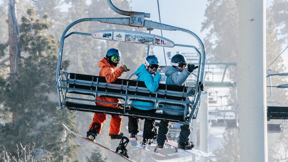 Three people with snowboards and wearing snow gear turn to look at the camera behind them while they're seated on a chairlift as it moves up a mountain.