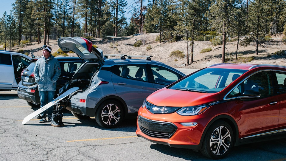 A line of Bolt EVs in a parking lot in the mountains. People are unloading a snowboard and other gear from the back of one of the Bolt EVs.