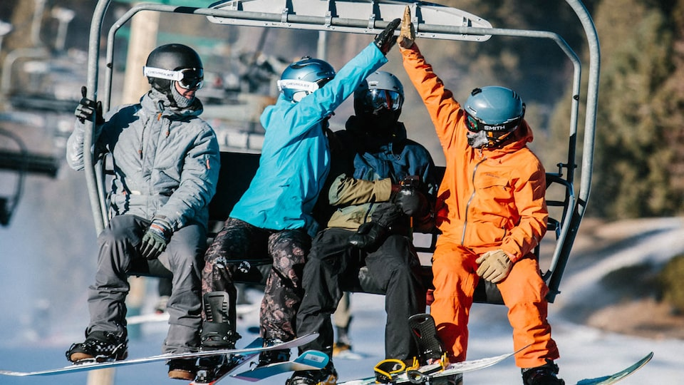 Two people on a chairlift high-five each other while two others look on.