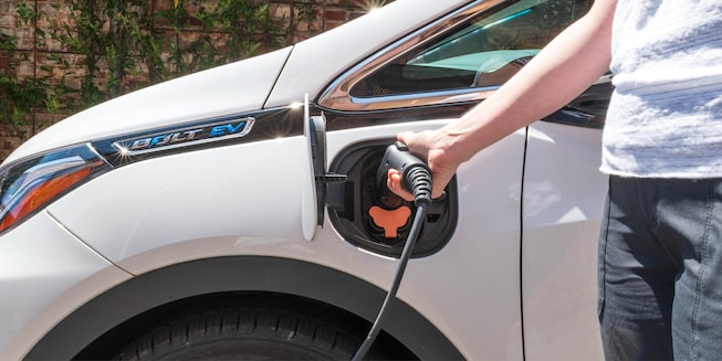 A woman's arm is seen plugging a charging cable into the side of a white Bolt EV.