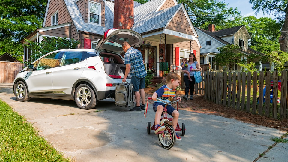 A man loads a suitcase into the open hatch of a white Bolt EV in a driveway in front of a brown house. A woman carrying a small child walks through a gate to the driveway while another child rides a tricycle in the driveway.