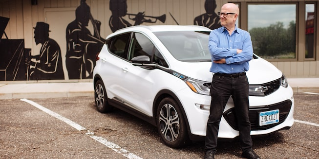A man stands in front of a Bolt EV.
