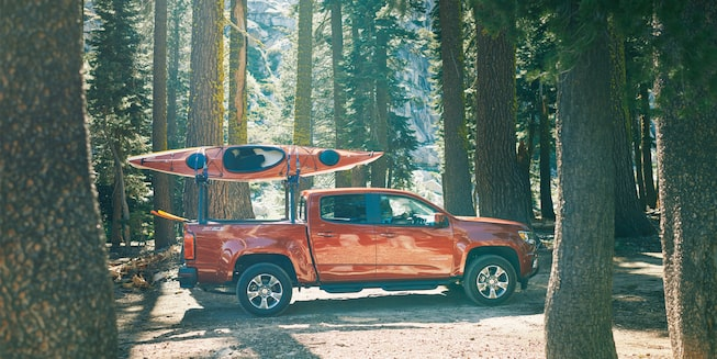 A Chevy Colorado with two kayaks on a gear rack drives through the forest.