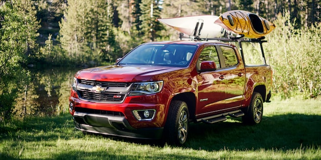A Chevy Colorado with two kayaks on a gear rack parked next to the woods.