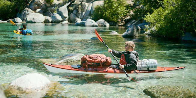 Two kayakers paddling near the shore of Lake Tahoe.