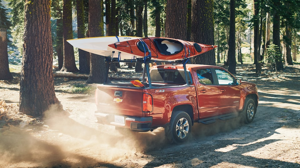 A Chevy Colorado with two kayaks on its rack drives through the forest.
