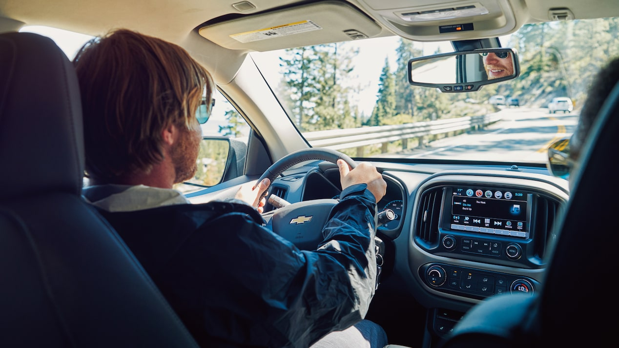 An interior shot of a man driving a Chevy Colorado down a coastal road.