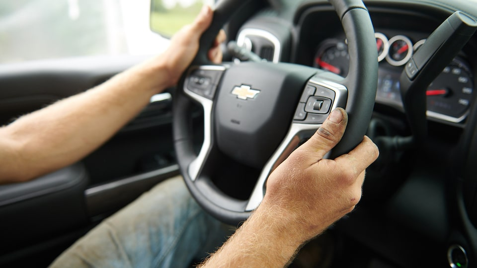 A close-up photograph of a man's hands holding the 2019 Silverado's steering wheel.