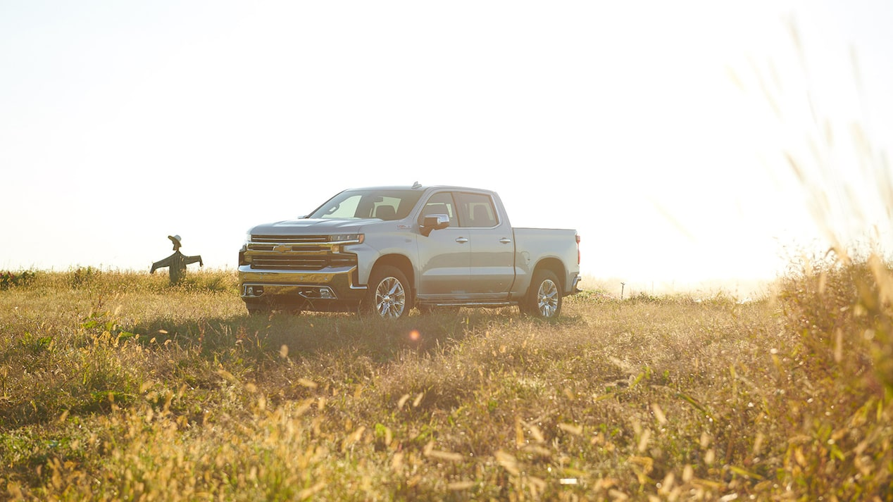 A 2019 Chevy Silverado Crew Cab parked in a field with a scarecrow in the background.