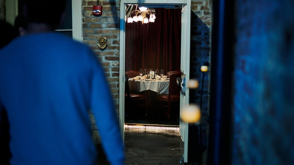 A table set with dishes and glassware, seen through an open doorway, sits unoccupied in Muriel's Jackson Square restaurant in New Orleans.