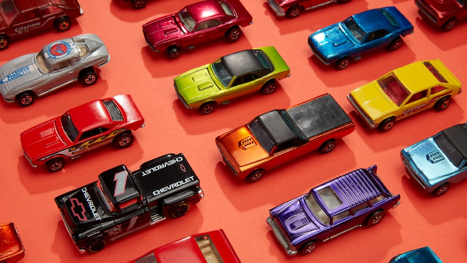 Rows of different types and colors of Hot Wheels cars lined up on an orange background.
