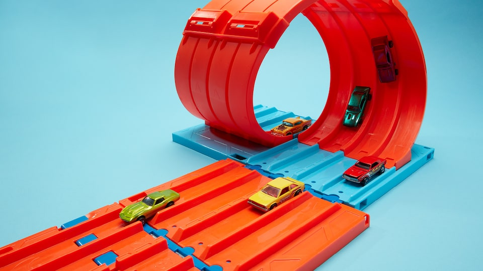 Several Hot Wheels on a fivelane orange Hot Wheels track with a loop.