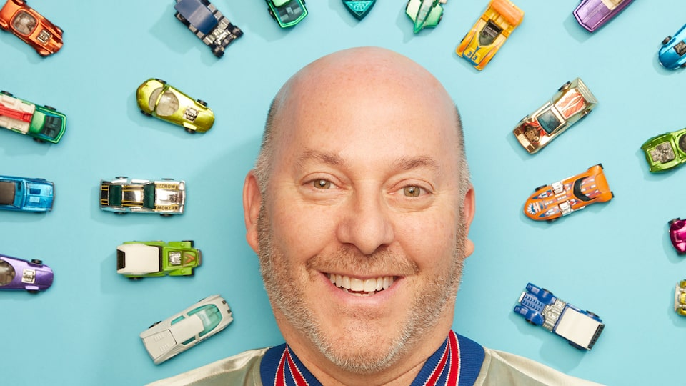 A head shot of Bruce Pascal in front of several Hot Wheels cars against a blue background.