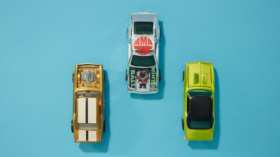 Three Hot Wheels cars seen from above on a blue background.