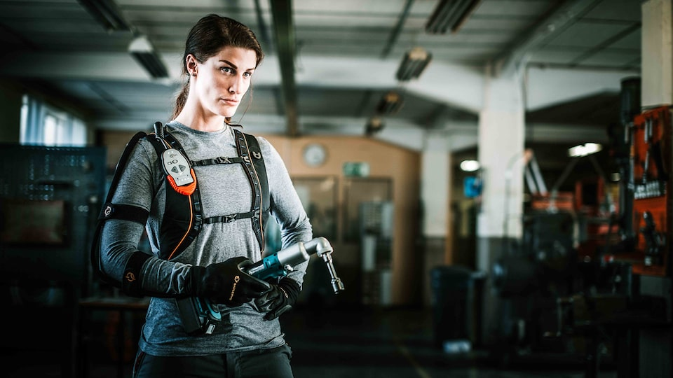 A woman wearing a high-tech exoskeleton suit on her upper body and high-tech gloves holds a tool in her right hand.