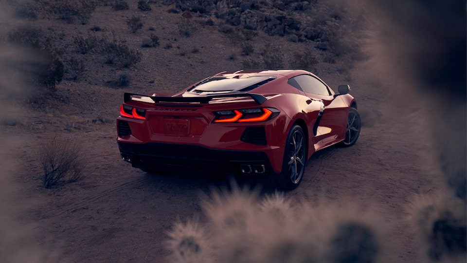 A Torch Red 2020 Corvette coupe in a desert landscape, seen from the rear with the brake lights illuminated.