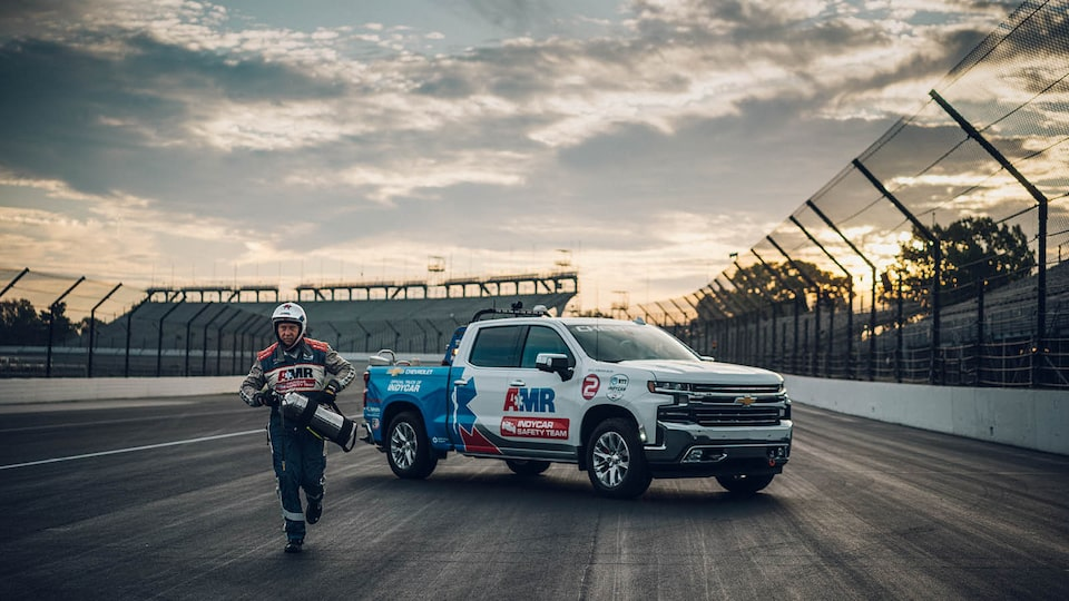 TIm Baughman carries a fire extinguisher as he runs away from a Chevrolet Silverado parked on the race track.