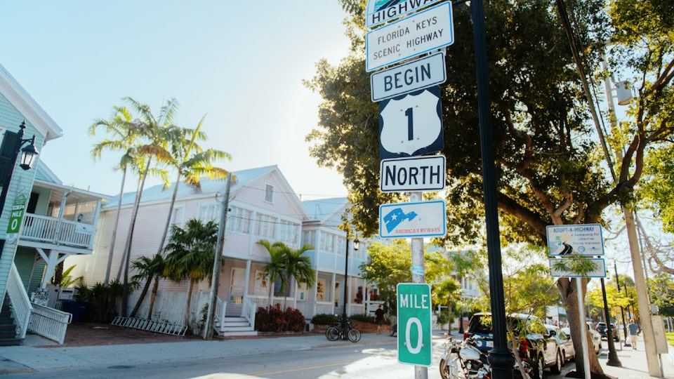 "A signpost that reads ""Florida Keys Scenic Highway. Begin Highway 1 North. Mile 0."" Pastel-colored buildings and palm trees are in the background."