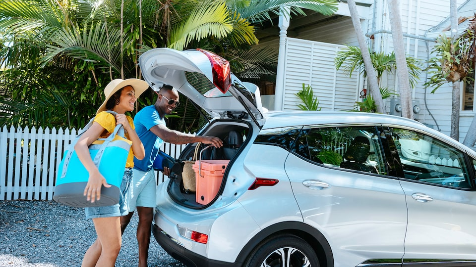 A woman and man wearing shorts and t-shirts and carrying beach gear load items into the  open back hatch of a Silver Ice Metallic Bolt EV.