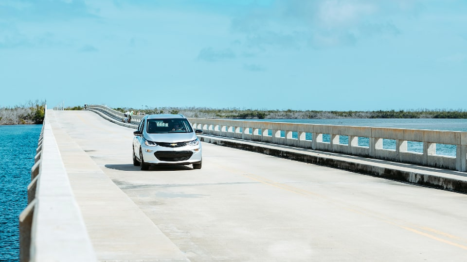 A Silver Ice Metallic Bolt EV drives across a causeway in the Florida Keys.