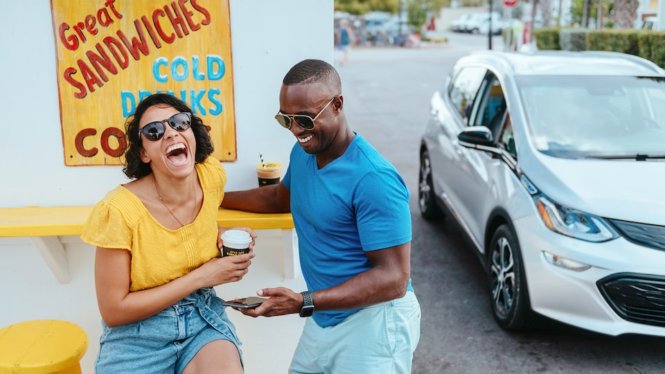 "A man and woman laugh together as they sit at a counter  in front of a sign reading ""Great sandwiches, cold drinks."" A Silver Ice Metallic Bolt EV is parked to the side."