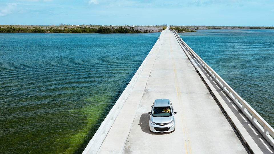 Seen from above, a Silver Ice Metallic Bolt EV drives across a causeway in the Florida Keys.