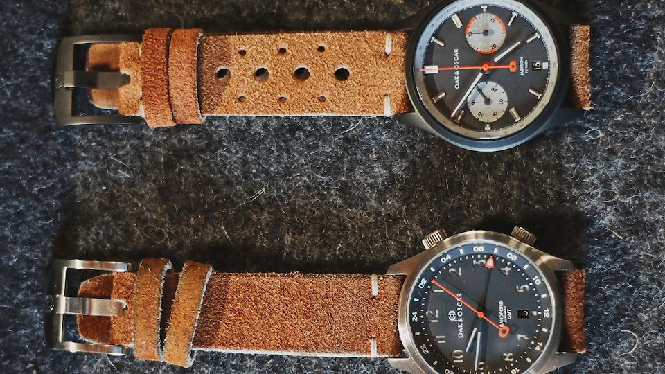 Two watches with brown leather straps lying on a table.