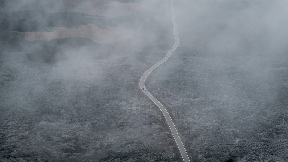 A drone shot of a strip of pavement winding through a field of black lava rock, seen through fog.