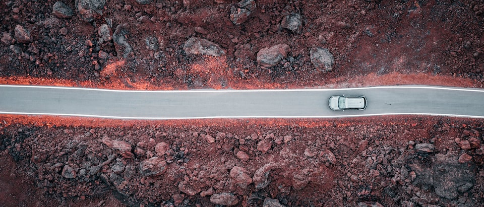 An overhead drone shot of a gray Chevrolet Blazer driving on a blacktop road through a field of lava rocks.
