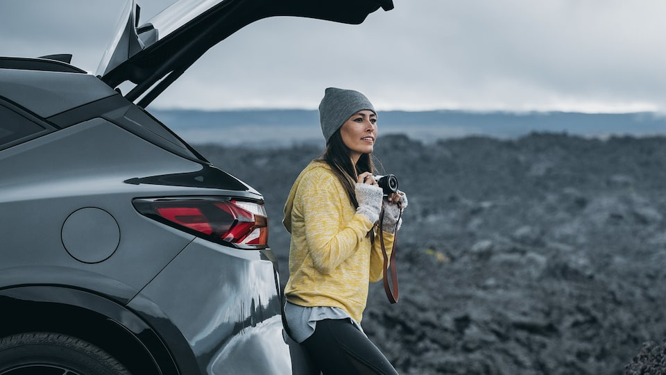 A woman wearing a sweater, hat and gloves holds a camera as she sits in the open tailgate area of a gray Chevrolet Blazer looking out at a surrounding field of black lava rocks.