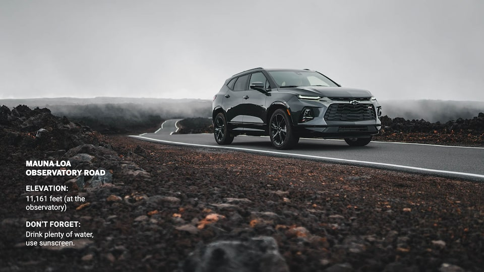 A gray Chevrolet Blazer drives on a narrow strip of pavement through a field of black lava rocks.