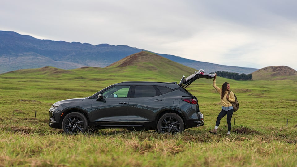 A woman stands behind a gray Chevrolet Blazer in an open, hilly field with mountains in the background. She has one hand on the open tailgate.