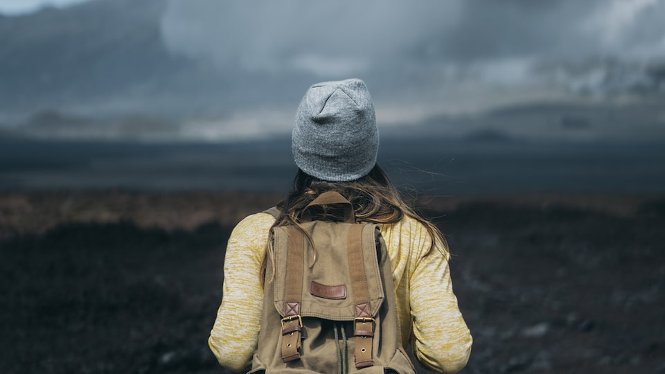 Seen from behind, a woman wearing a backpack and a hat looks out on a Hawaiian landscape of lava rocks, mountains, and clouds.