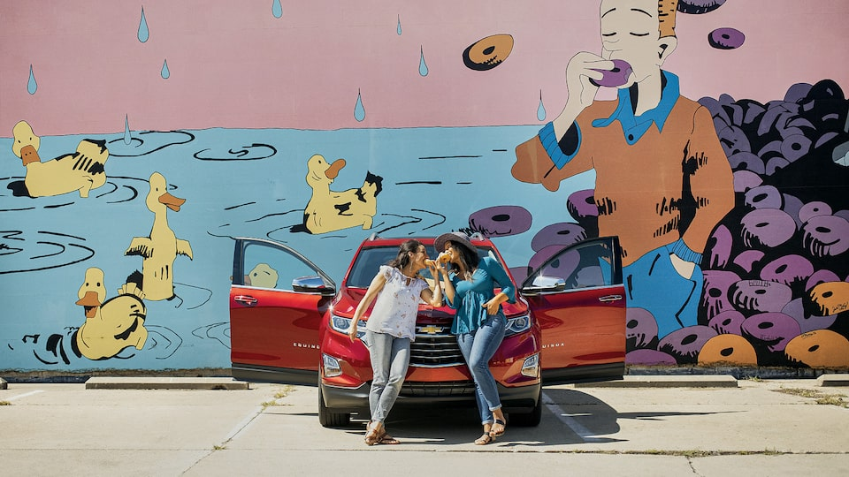 Two women lean against the front of a red Chevrolet Equinox while eating donuts. There is a mural on the wall behind them of a man eating a donut and ducks swimming in water.