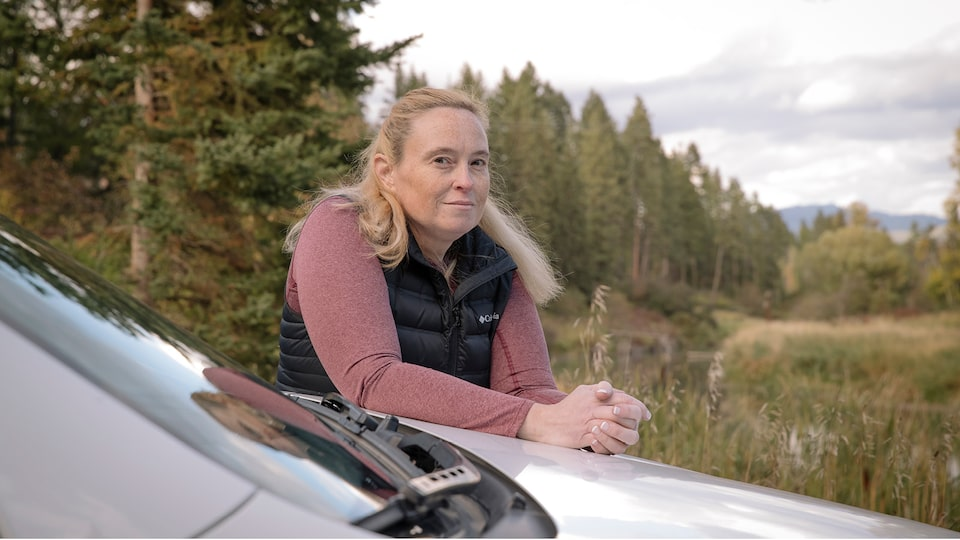 OnStar Member Jennifer Allen stands outside her truck leaning on the hood in a scenic area with evergreen trees in the background.