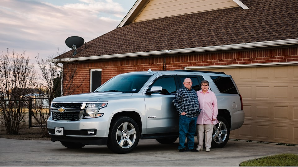 OnStar Members David and Cheryl Roberts stand next to their silver Chevy Tahoe in their driveway.