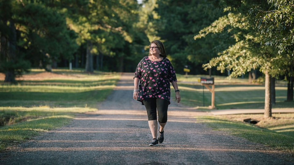 OnStar Member Teresa Moore walks down a rural gravel road.