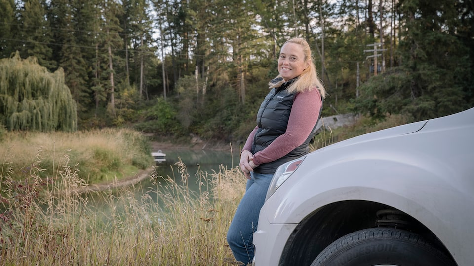 OnStar Member Jennifer Allen leans on the front of her truck with a field and trees in the background.
