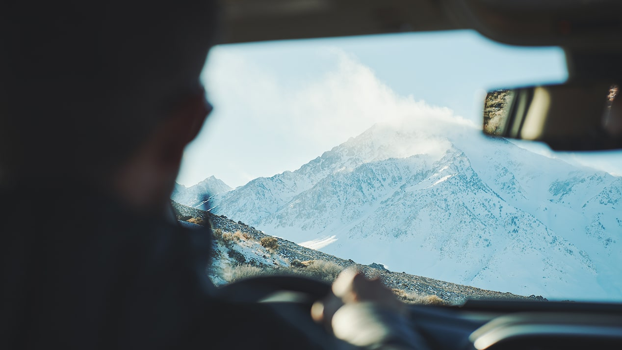 A snowy mountaintop against a blue sky is seen from the back seat of a Chevy Colorado pickup truck, looking over the driver's shoulder.