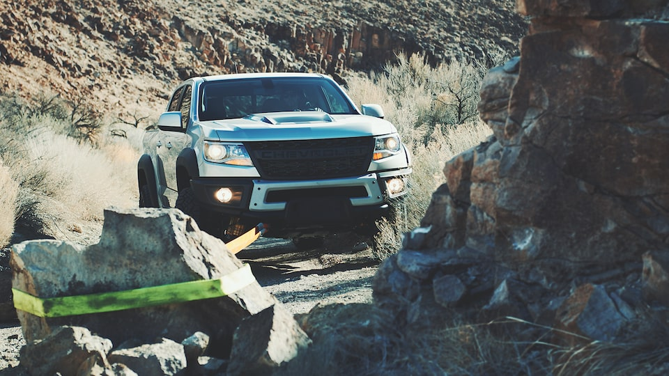 A silver Chevy Colorado ZR2 Bison pickup truck in the California desert is hauling a large boulder off a pathway using a strap connected to the front of the truck.