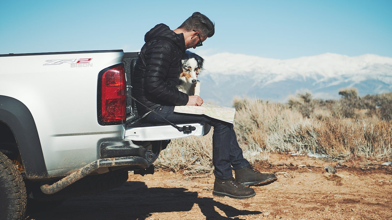 A man and a dog sit on the tailgate of a silver Chevy Colorado ZR2 Bison pickup truck with snow-capped mountains in the background.