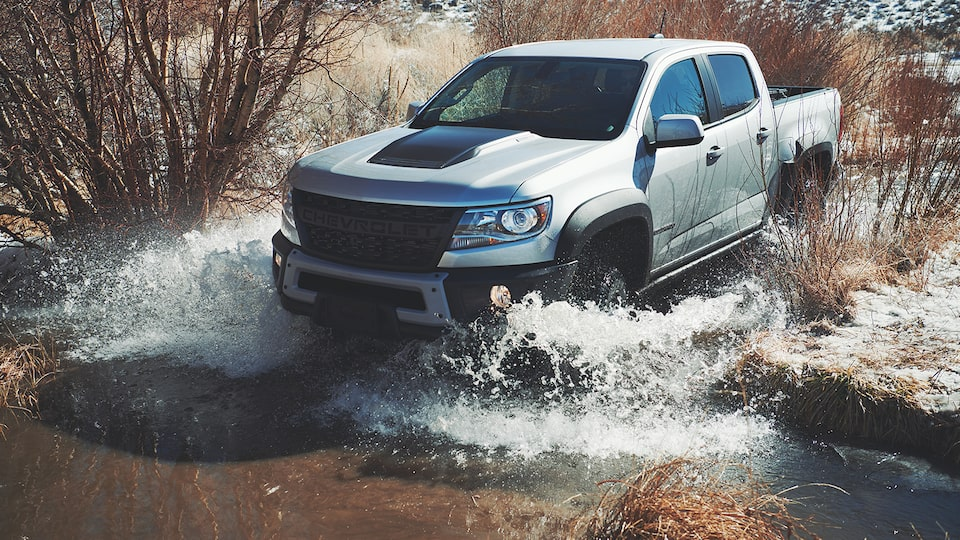 A silver Chevy Colorado ZR2 Bison pickup truck drives through shallow water with desert scrub bush around it.