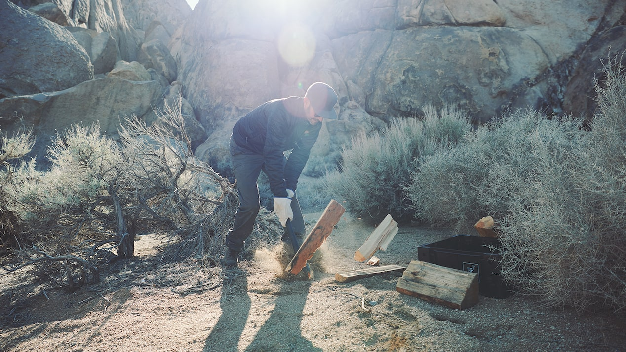 A man wearing work gloves chops wood in front of boulders and desert sagebrush.