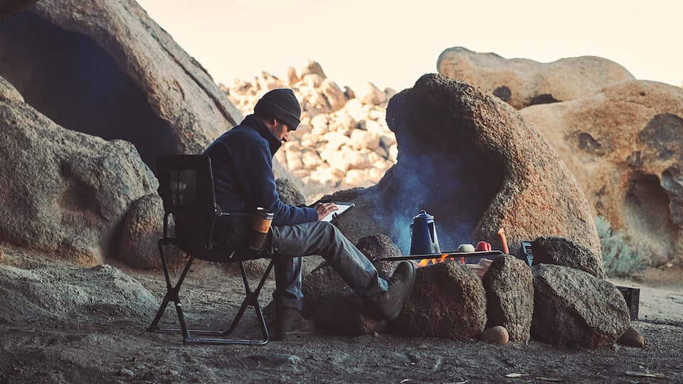 A man sits on a camp chair amid large boulders next to a campfire. There is a coffeepot on the fire.