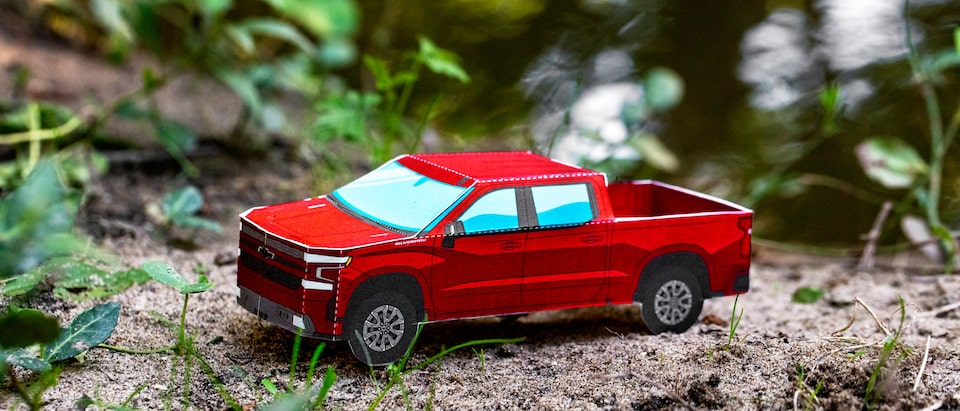 A miniature paper model of a Cajun Red 2020 Silverado RST Diesel sitting on bare ground with grass and leaves in the background.